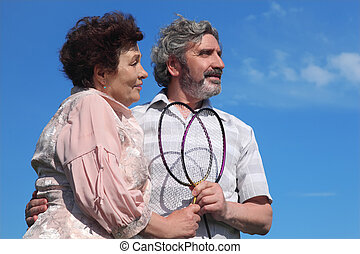 old man and woman embracing, holding badminton rackets, blue sky