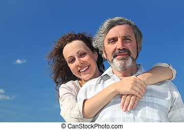 adult daughter embracing her father from back and smiling, blue sky