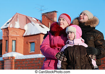 father, mother and daughter standing outdoors in winter near house and looking in sky, focus on girl