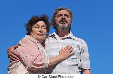 old woman and man standing and embracing, blue sky