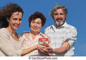 adult daughter and her parents holding house model and smiling, blue sky