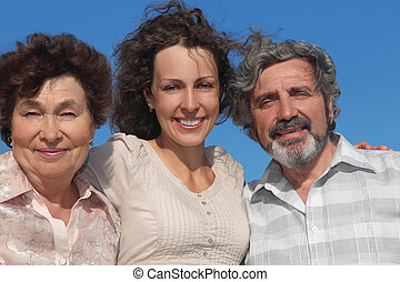 portrait of adult daughter and her parents smiling, blue sky