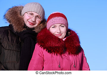 beautiful young woman in pink jacket and man in glasses at winter outdoors, focus on woman