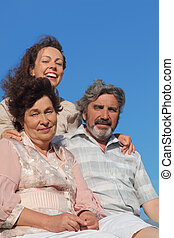 adult daughter embracing her parents and smiling, blue sky, focus on mother