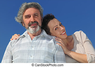 portrait of young woman leaning to her father from back and smiling, blue sky