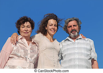 portrait of adult daughter and her parents embracing, blue sky