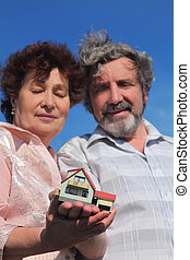old man and woman holding little model of house, blue sky, focus on house