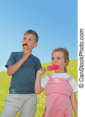 little boy and girl eating ice-creams, blue sky and green lawn, focus on girl