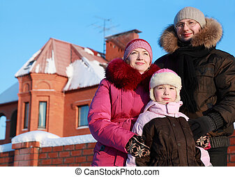 father, mother and daughter standing outdoors in winter near...