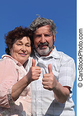 old man and woman making thumbs up gesture, blue sky