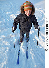 little boy in warm sport clothes skiing and smiling at...