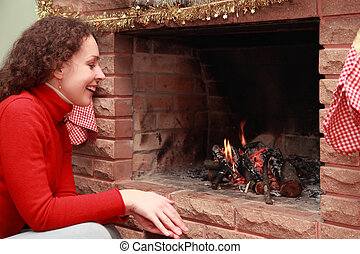 beautiful young woman in red sweater sits near fireplace and...