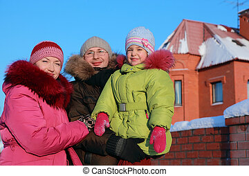 father, mother and daughter standing outdoors in winter near house, father and father holding daughter in hands