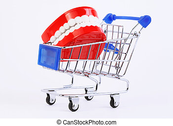 small toy jaw with white teeth in purchasing cart on white...