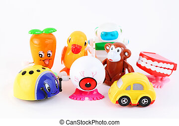 group of eight small bright clockwork toys on white...