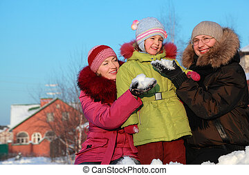 father and mother offer to daughter to make snowball outdoors in winter near house, father and mother sitting