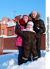 father, mother and daughter standing outdoors in winter near house, father and mother holding daughter's hands
