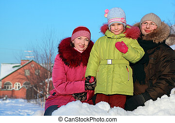 father, mother and daughter standing outdoors in winter near house, mother holding daughter hand