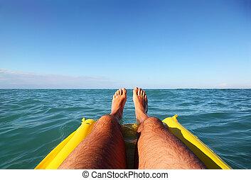 men's feet on yellow inflatable mattress, ocean, far horizon