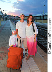mother, father and little daughter with bag on platform of railway at evening