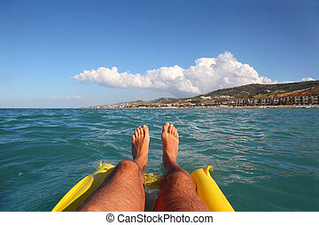 mens feet on yellow inflatable mattress, sea, far shore and...