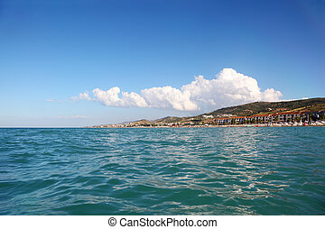 blue water of sea, far away beach, mountains and building of...