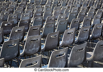 Many rows of gray, plastic chairs on Piazza San Pietro in Rome, Italy.
