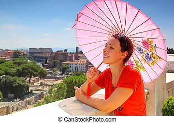 beautiful young woman with pink umbrella looks at Rome from Altar of Fatherland in Rome, Italy.