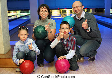 Family of squatting in bowling club and shows hands of ok,...