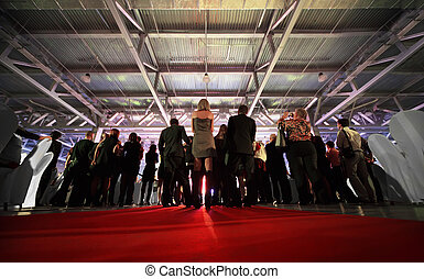 Crowd of spectators look at stage in evening; backs of...