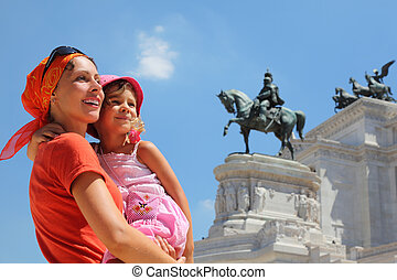 Mother is holding little daughter, equestrian monument to Victor Emmanue II near Altar of fatherland in Rome, Italy