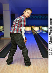Boy looks back and qualify to throw  ball for bowling