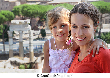 beautiful young mother and litte daughter, ancient ruins in...