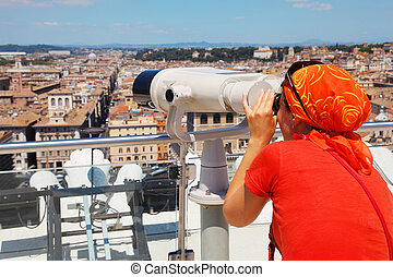 Woman in red wear looking through big binoculars, color panorama of Rome from altar of fatherland, catholic basilics, streets and houses, Italy
