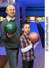 Father and son in glasses stands sideways and holds balls...