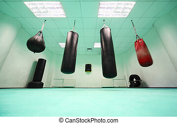empty light green room, where black and red punching bag...