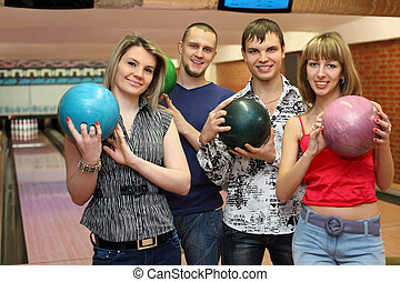 Two fellows and two girls stand in club and hold balls for bowling, focus on fellow on left