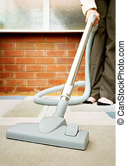 woman vacuuming - woman doing housework, vacuuming the...