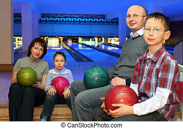 Mother, father and two children, sit in club and hold balls...