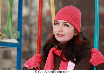 beautiful young woman in pink hat sitting on swing in winter, children's playground