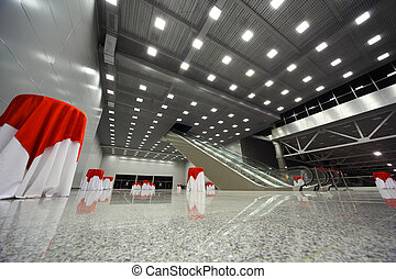 Table covered with white-red tablecloth in large, empty lobby with escalator
