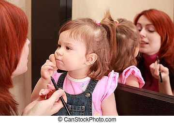 little daughter powders, mother makes make-up near mirror, woman in pink shirt