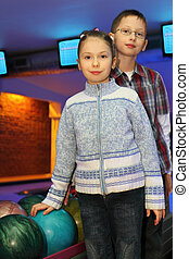 Brother and sister stand alongside near balls for bowling,...