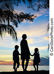 Silhouettes of mother and two kids at sunset