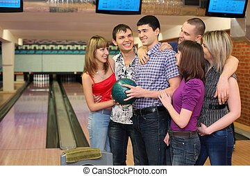 One fellow holds ball for bowling and his friends stand alongside with him and all look at him, focus on  man in center.