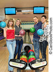 Four students stand near tenpin bowling with balls for...