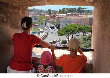 Young beautiful mother, son and daughter looking through window in Sant' Angelo Castel. View of Rome. Focus on panorama