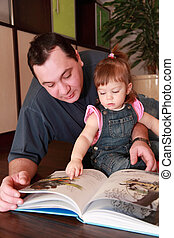 father and little daughter in denim jumpsuit reads book on brown floor, focus on girl