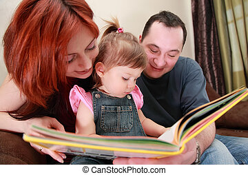 father and little daughter in denim jumpsuit reads book on brown sofa, focus on girl