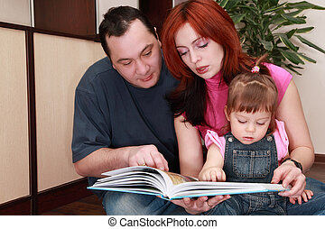 mother, father and little daughter in denim jumpsuit reads book, houseplant, focus on girl